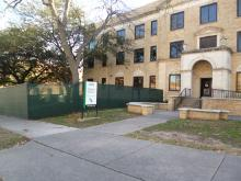 An image of the front entrance of Terrill Hall. Construction fencing has already been placed around the building.